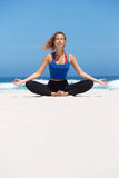Woman sitting in yoga position at the beach Stock Image
