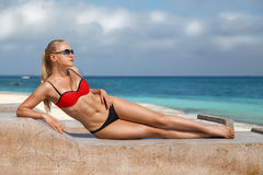 Woman sitting on the Zanzibar& x27;s beach. Beautiful blonde woman in the red bikini and sunglasses sitting on the lonely evening beach with turquoise water Royalty Free Stock Photos