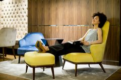 Woman sittinh on a yellow chair and reading a book. Young woman sittinh on a yellow chair and reading a book Stock Photo