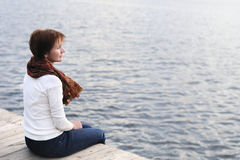 A woman is sittng on wood boards by the water Royalty Free Stock Images