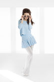 Woman Sixties Style. Retro sixties style woman with long hair posing over elegant studio background. Blue fashion outfit with skirt, old-fasihoned round Stock Photos
