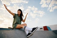 Woman skateboarder enjoying a day at skate park. Beautiful woman sitting over a skateboard on ramp in skate park looking away and laughing. Woman skateboarder Royalty Free Stock Photography