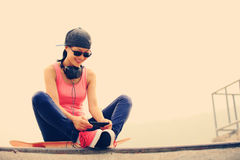 Woman skateboarder listening music Stock Photos