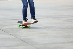 Woman skateboarder riding skateboard on city Stock Photos