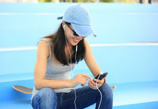Woman skateboarder sit on skatepark stairs listening music Royalty Free Stock Photography