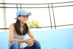 Woman skateboarder sit on skatepark stairs listening music Royalty Free Stock Photos