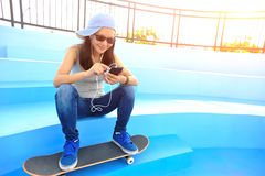 Woman skateboarder sit on skatepark stairs listening music Royalty Free Stock Image