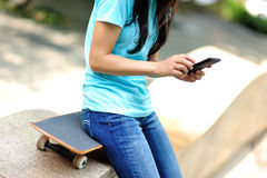 Woman skateboarder sit use her cellphone Stock Photo