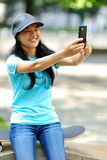Woman skateboarder sit use her cellphone Royalty Free Stock Image