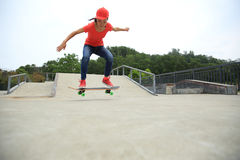 Woman skateboarder skateboarding at skate park Royalty Free Stock Photography