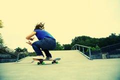 Woman skateboarder skateboarding at skate park Stock Images