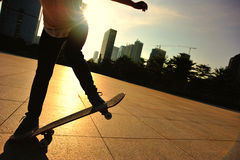 Woman skateboarder skateboarding at sunrise city Stock Images