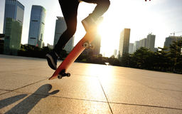 Woman skateboarder skateboarding at sunrise city Stock Photos