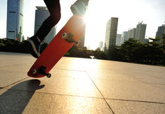 Woman skateboarder skateboarding at sunrise city Royalty Free Stock Images