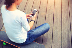 Woman skateboarder use cellphone taking photo Stock Image
