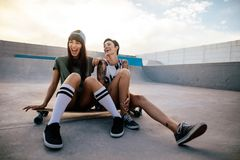 Female skaters friends hangout at skate park. Woman skateboarders laughing and having fun. Two female skaters friends hangout at the skate park Stock Images