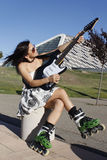 Woman with skates playing the guitar. In Spain, Zaragoza Royalty Free Stock Photo