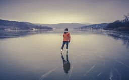 Woman skating alone on a frozen lake in winter