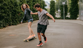 Woman skating on a basketball court with friend Stock Image