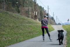 Woman is skating on rollerblades beside her dog outdoors. Stock Photo