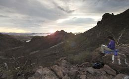 A Woman Sketches the Sunrise on Tetakawi Mountain Above Los Algo. Dones, Mexico stock photos