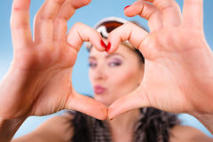 Woman in ski goggles making heart symbol fingers Royalty Free Stock Photography