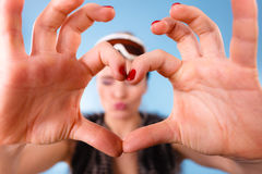Woman in ski goggles making heart symbol fingers Stock Image