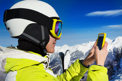 Woman in ski mask and helmet use cell phone Royalty Free Stock Images