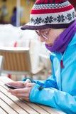 Woman in ski resort using smartphone. Stock Image
