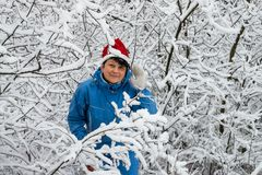 Woman in ski suit and cap of Santa Klaus  in snow-covered wood Royalty Free Stock Photo