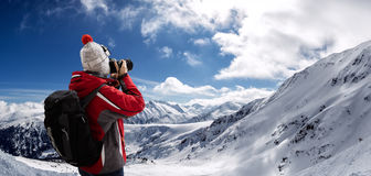 Woman in ski suit takes picture Royalty Free Stock Photo