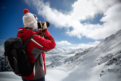 Woman in ski suit takes picture Royalty Free Stock Photos