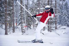 Woman on a ski tow in red and white skiing suite waving with her Stock Images