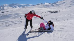 Woman Skier Helps The Other To Rise To Her Feet After Falling On The Ski Slope. A woman skier fell on the slope. Helping her to stand up, another woman takes his stock video footage