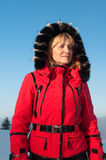 Woman skier in the mountains in red winter jacket Royalty Free Stock Photos