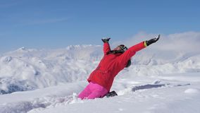 A Woman Skier Falls In The Snow With A Pleasure, Super Slow Motion 180 Fps. A woman skier in a red coat and pink trousers sits and then falls slowly down in the stock footage