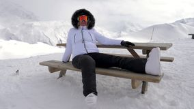 Woman skier pleasure relax in the mountains sitting on bench. A woman skier is relaxes and enjoys her day off outdoors. She sitting on the wooden bench in white stock video