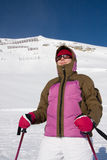 Woman skier in ski suit standing in front of mount Royalty Free Stock Photo