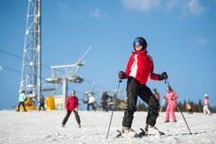 Woman skier with ski at winer resort in sunny day Royalty Free Stock Image