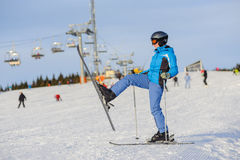 Woman skier skiing downhill at ski resort against ski-lift Stock Images