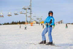 Woman skier skiing downhill at ski resort against ski-lift Royalty Free Stock Photos