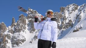 Woman skier with skis on her shoulder admires beauty of nature in the mountains stock photos