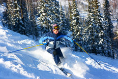 Woman skier on the slope. Skier on the slope near trees. A lot of snow and speed Royalty Free Stock Photos