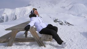 Woman Skier Pleasure to Relax in the Mountains on a Sunny Day Sitting on Bench stock photography