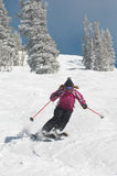 Woman Skiing Down Snow Covered Slope. Full length of a young woman skiing down snow covered slope Royalty Free Stock Photography