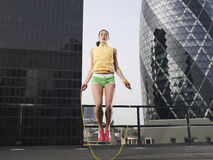 Woman Skipping Against Downtown Buildings Stock Photography