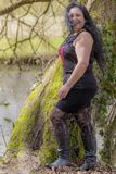 Woman with skirt and black blouse with her hair disheveled by the wind next to a trunk of a tree with moss. Beautiful woman with skirt and black blouse with her stock photography