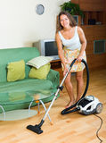 Woman in skirt cleaning with vacuum cleaner Royalty Free Stock Photo