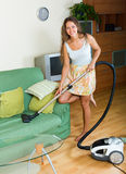 Woman in skirt cleaning with vacuum cleaner Royalty Free Stock Photos