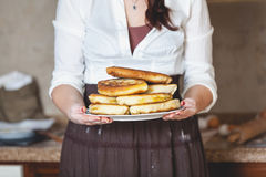 Woman holds plate with fried pies royalty free stock photography